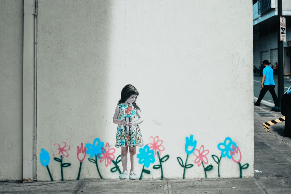 girl in white and pink floral dress standing beside wall with pink flower