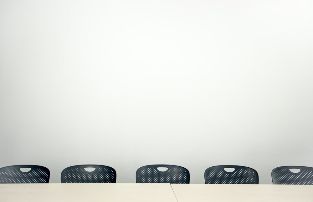 3 black chairs on white room