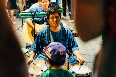 boy in blue and green crew neck shirt playing drum