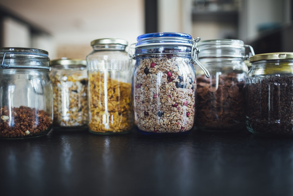 brown and white beans in clear glass jar