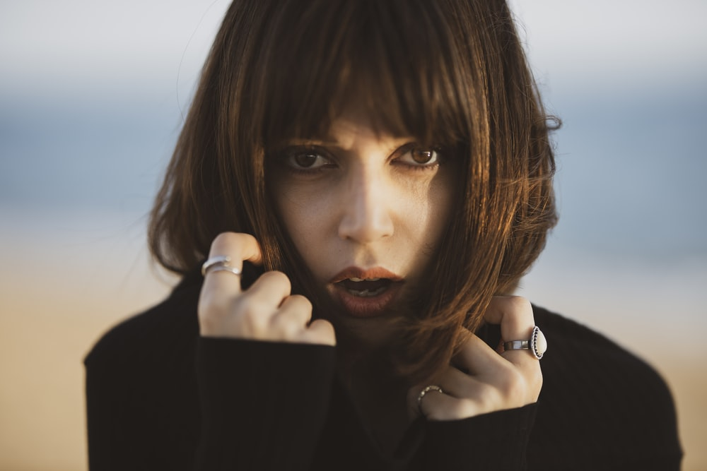 woman in black long sleeve shirt holding her chin