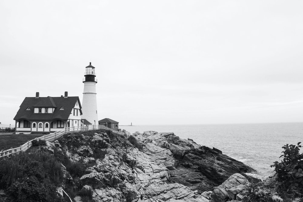 lighthouse on rock formation near body of water