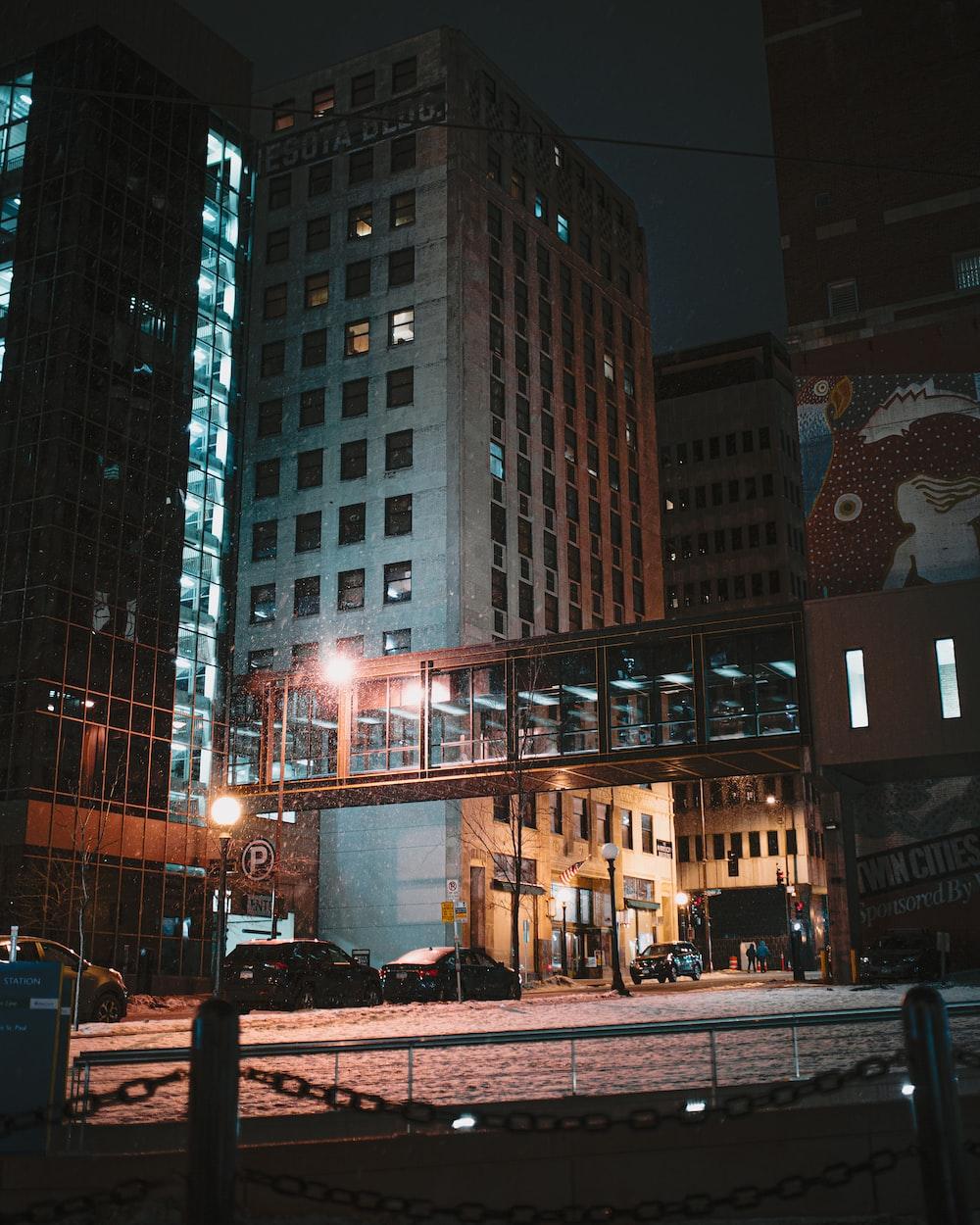 people walking on sidewalk near high rise buildings during night time