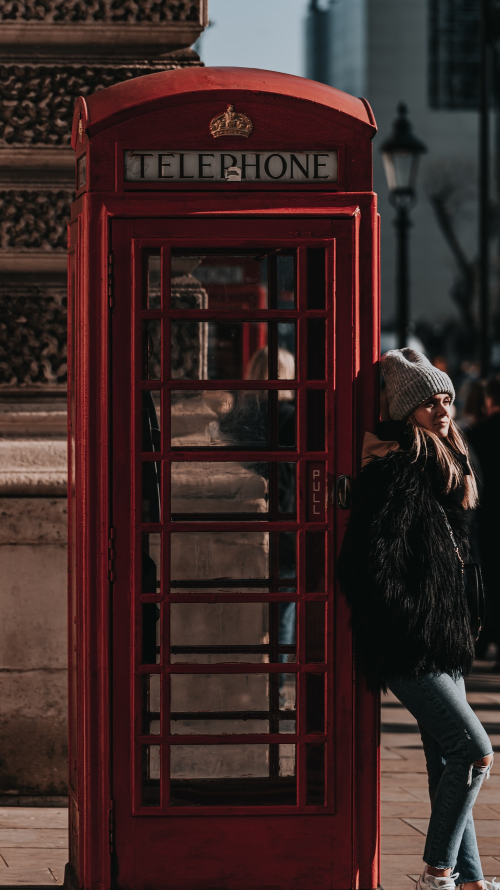 woman in black fur coat standing beside red telephone booth