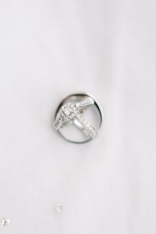 silver diamond ring on white textile