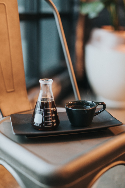 black ceramic mug on black laptop computer