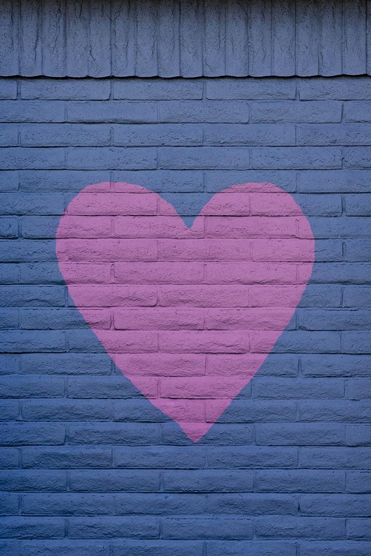 pink heart wall art on black brick wall