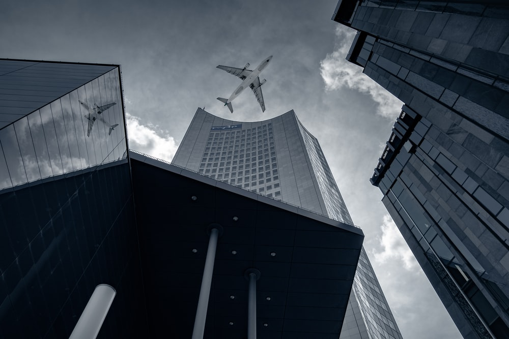 grayscale photo of airplane in flight over high rise buildings