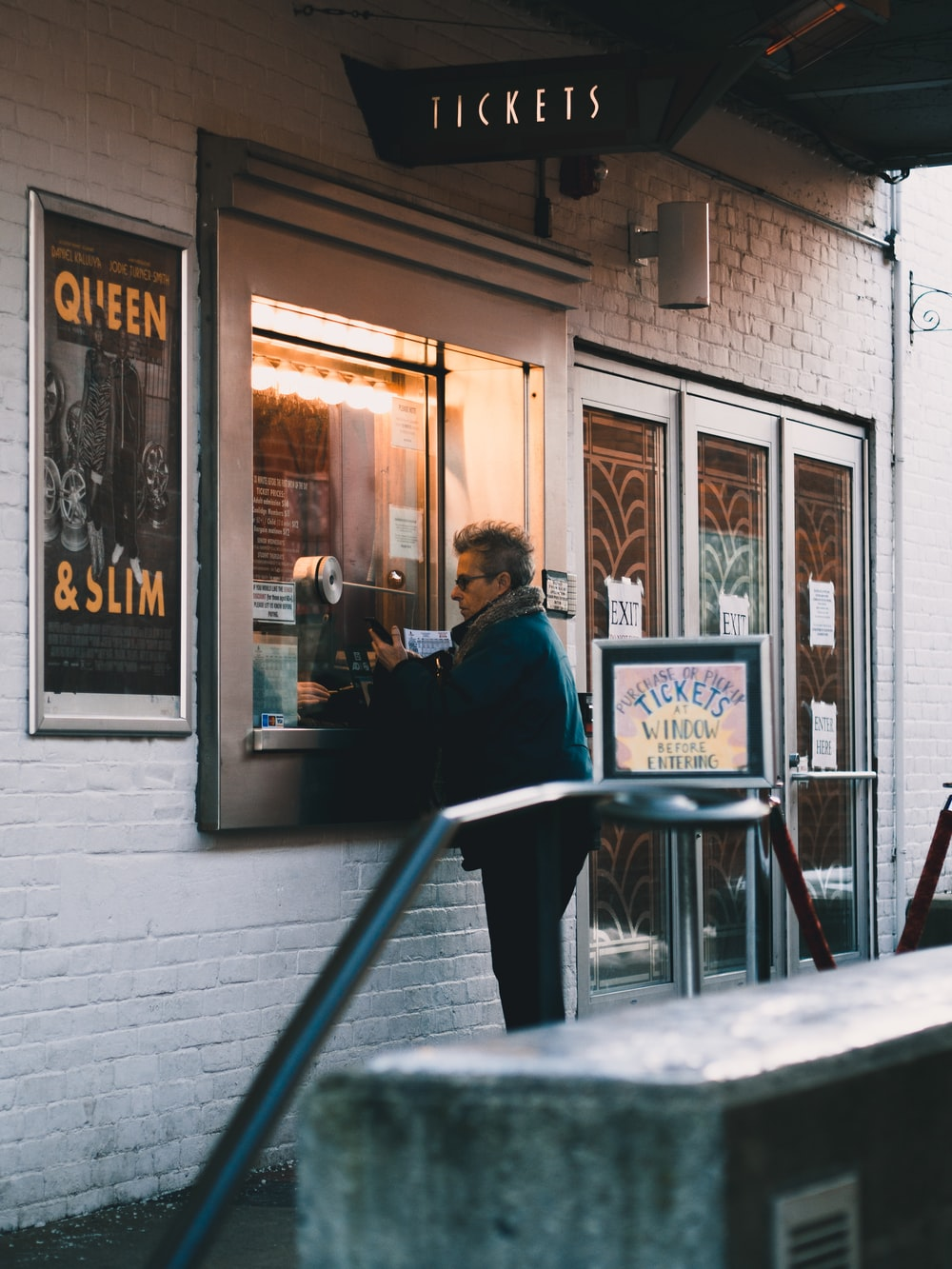 man in black jacket sitting on chair in front of store