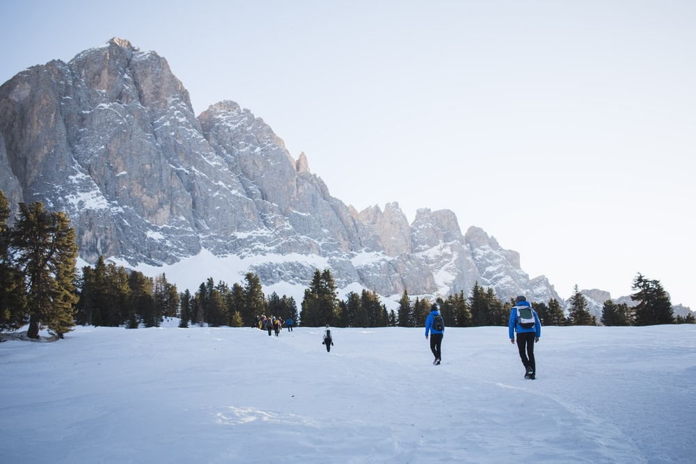 people walking on snow covered ground near trees and mountains during daytime