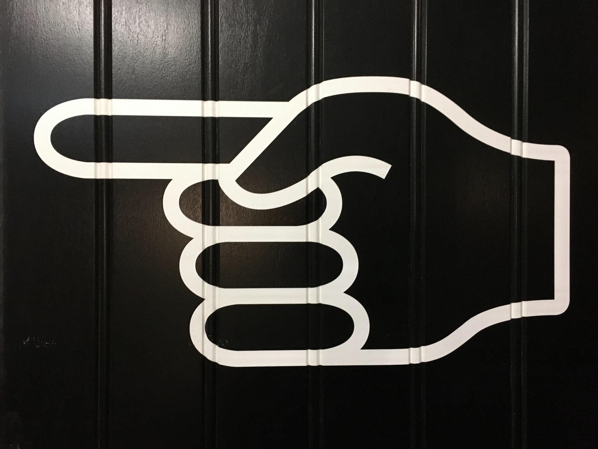 Fundo preto com pintura branca de uma mão fechada apontando para à esquerda