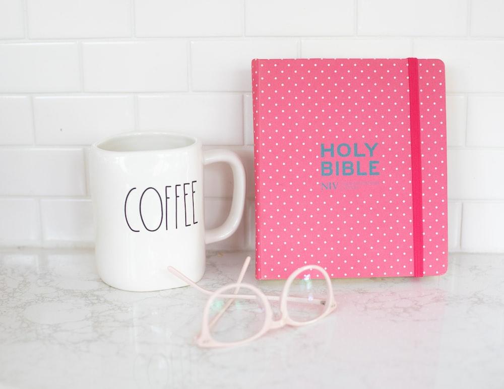white ceramic mug beside pink and white heart print box