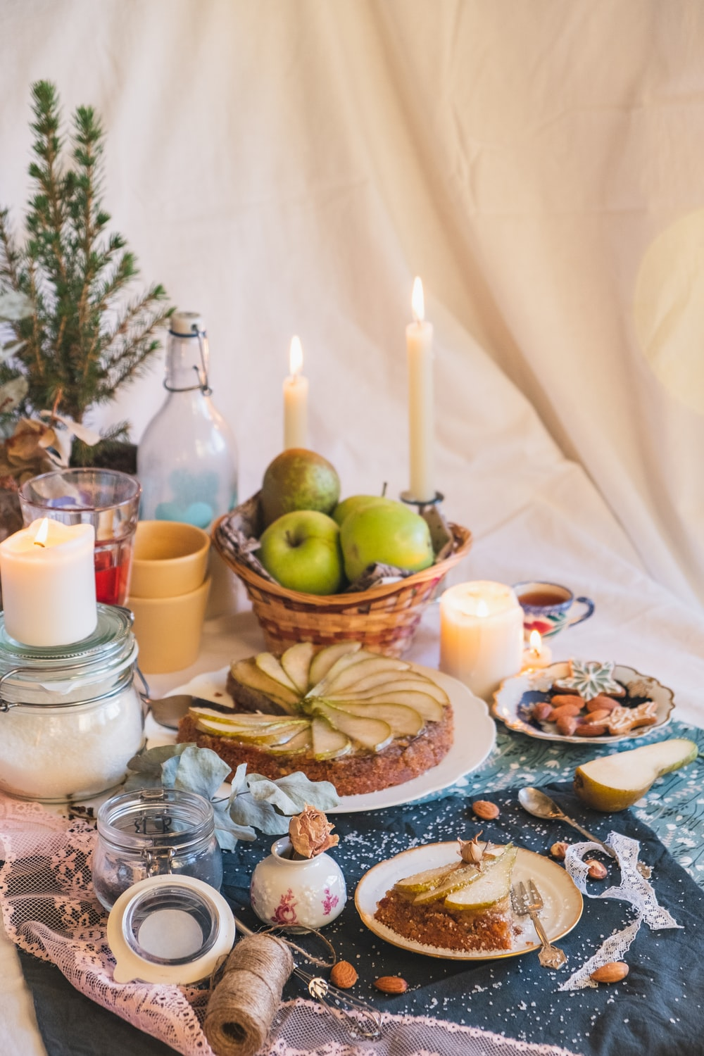 green apple fruit beside white pillar candles on brown wooden tray