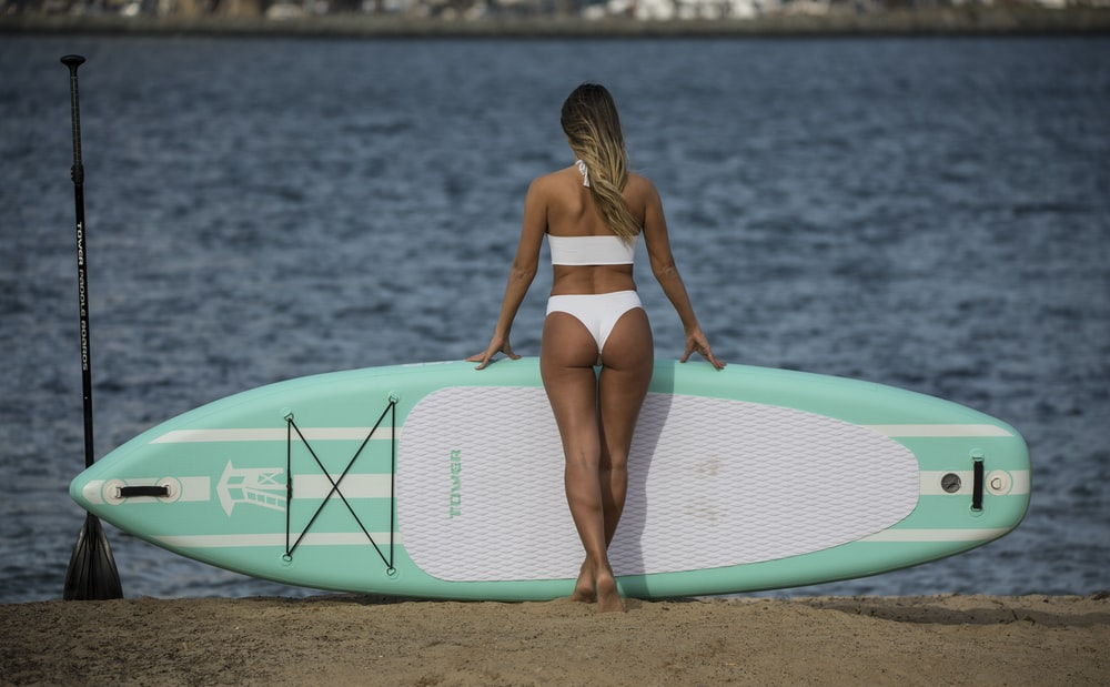woman in black and white bikini holding green surfboard on beach during daytime