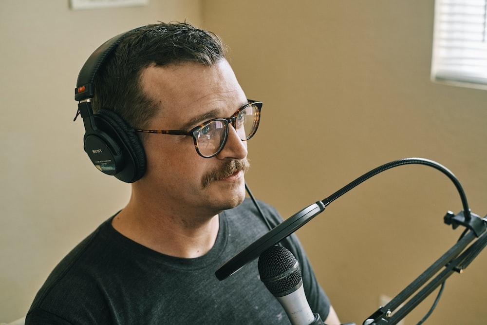man in black crew neck shirt wearing black headphones