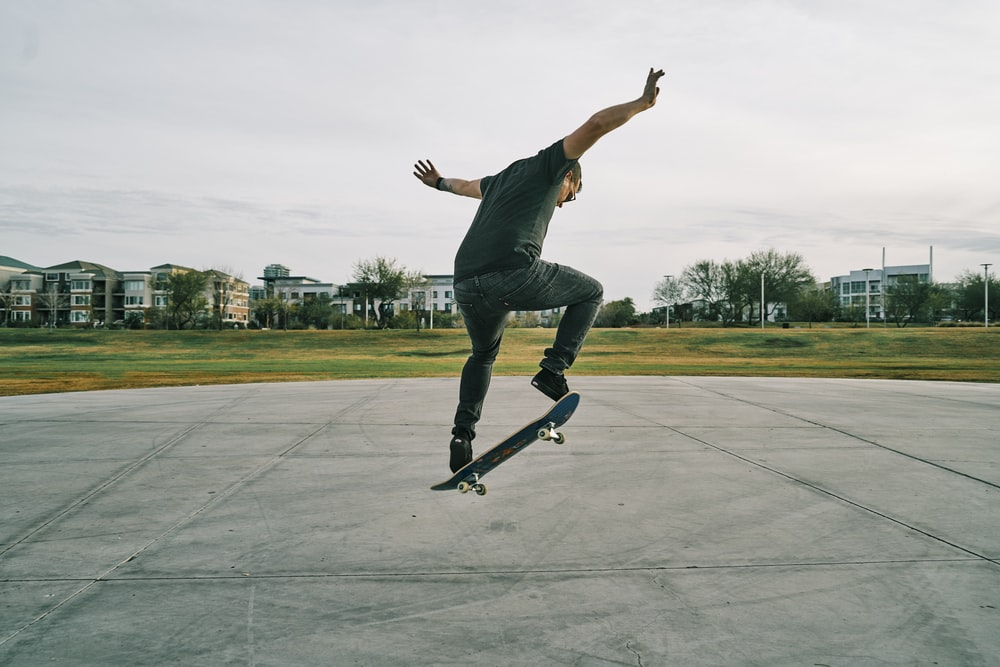 man in black t-shirt and blue denim jeans riding skateboard during daytime