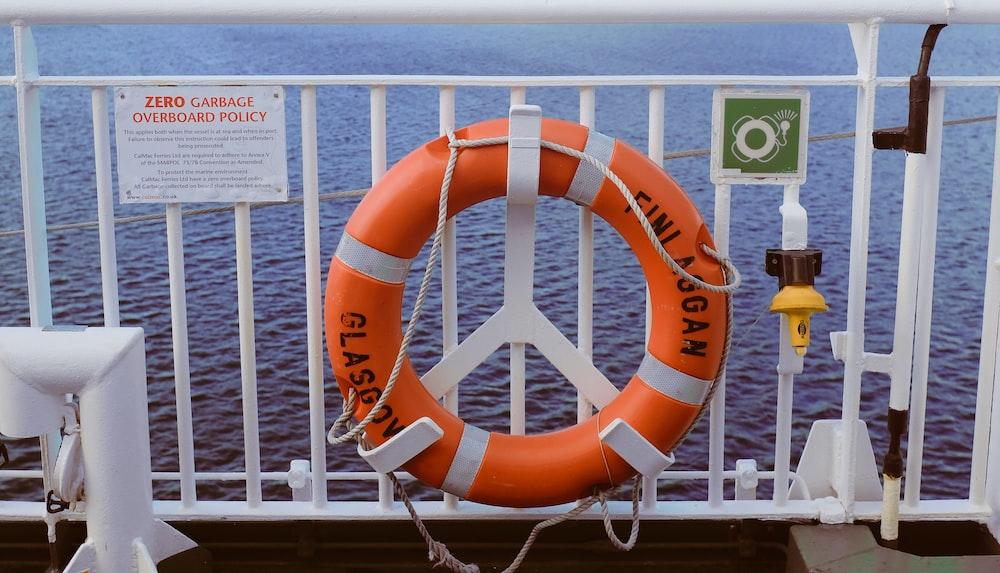 orange life buoy on white steel fence during daytime