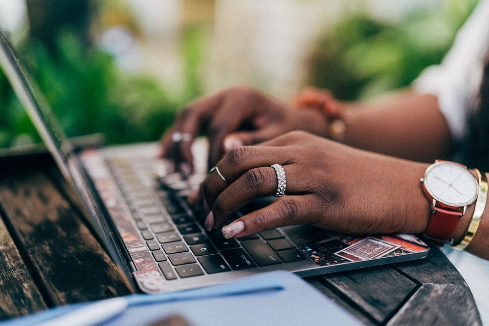 person wearing silver ring using macbook pro