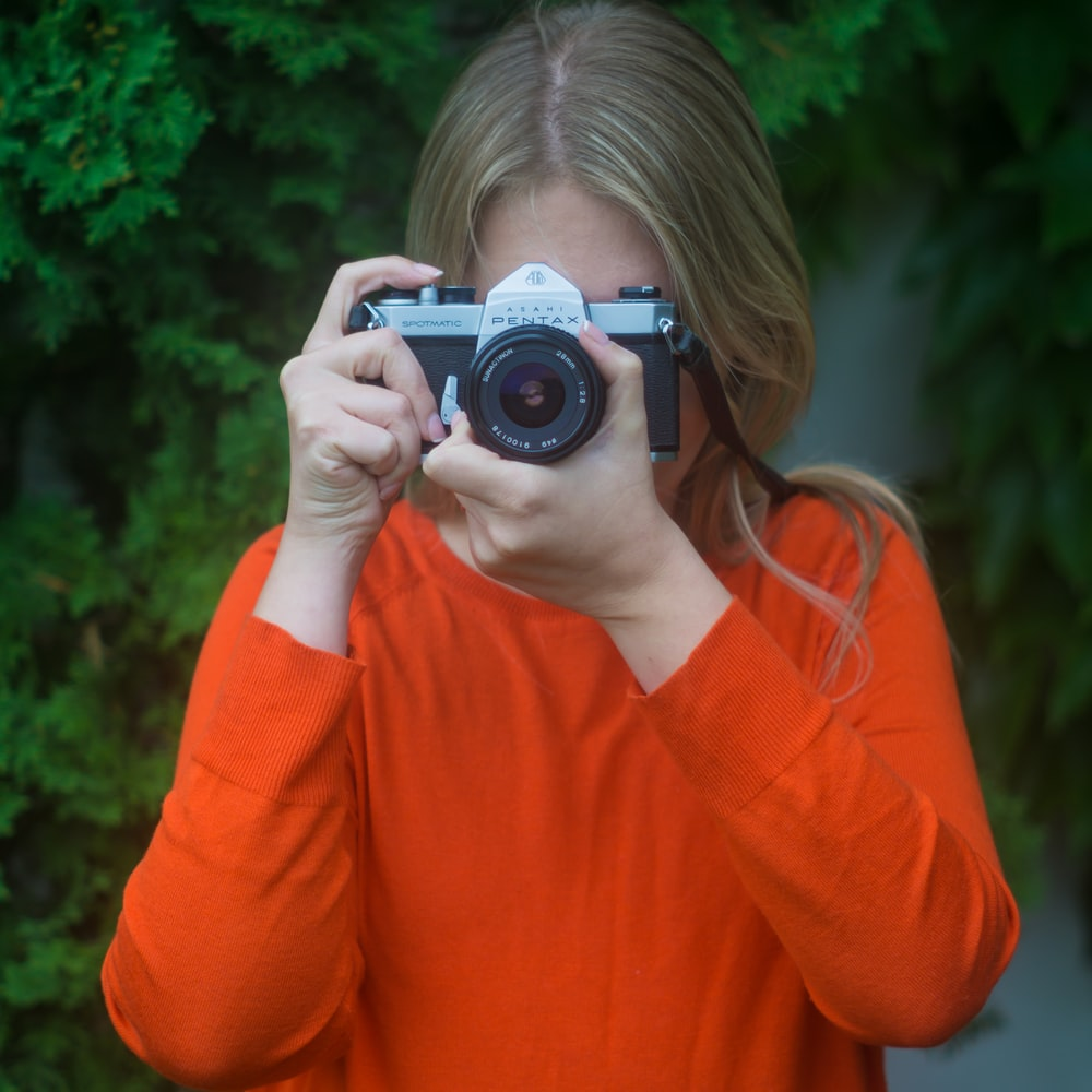 woman in orange long sleeve shirt holding black and silver camera