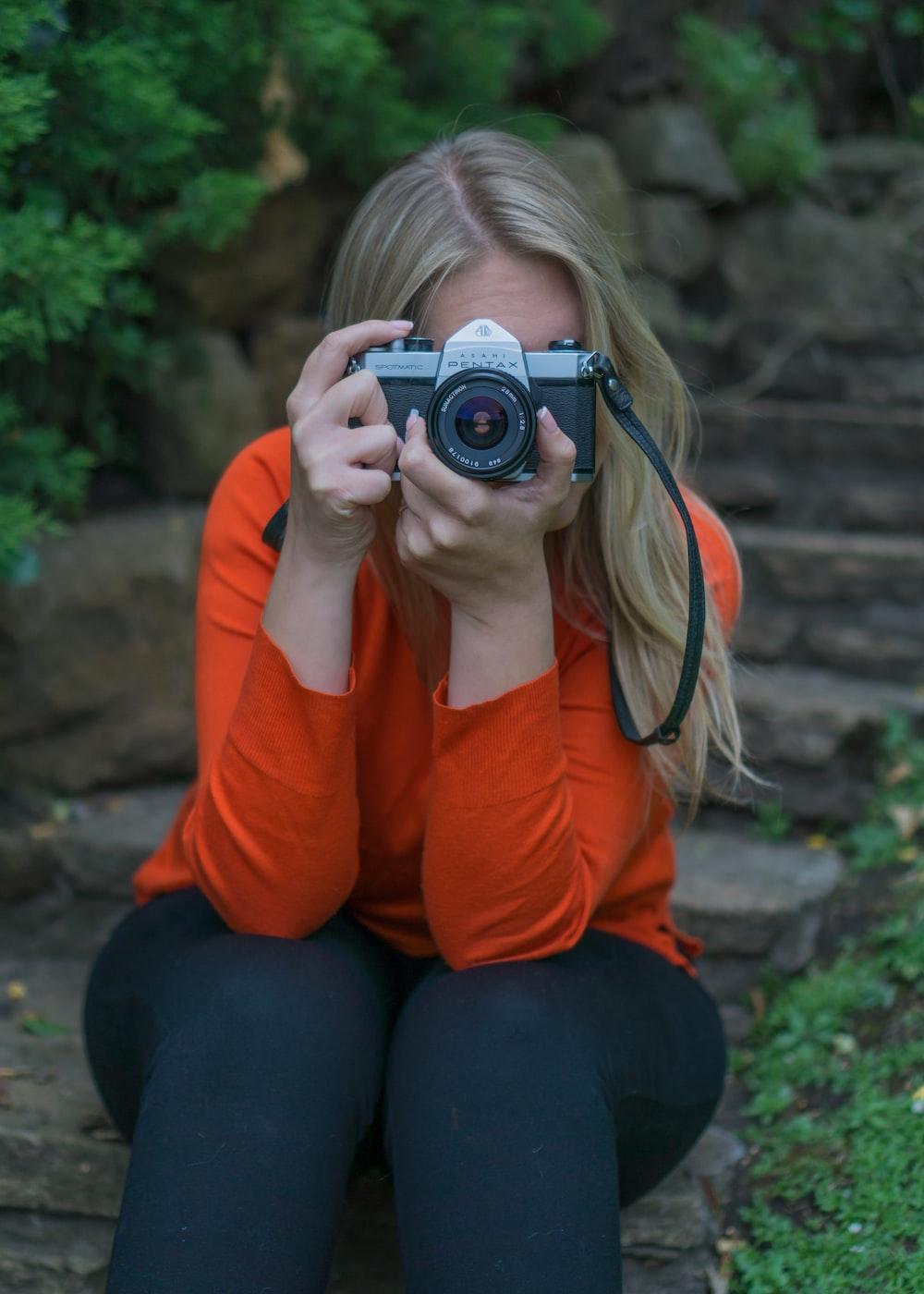 woman in orange long sleeve shirt and black pants holding black camera