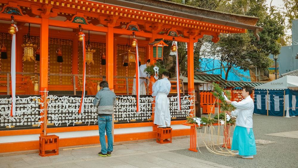 man in white dress shirt standing near brown wooden gate during daytime