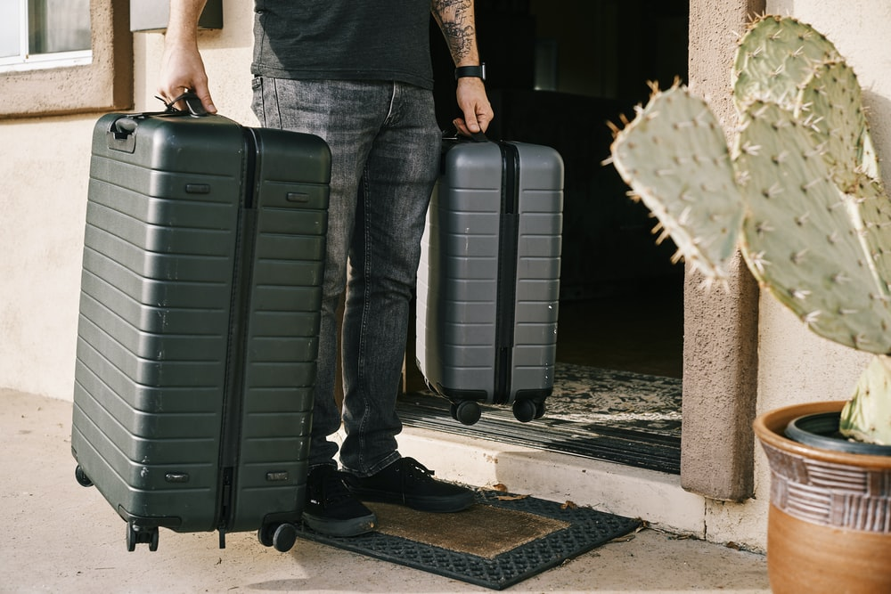 man in black denim jeans and black leather shoes standing beside black luggage bag
