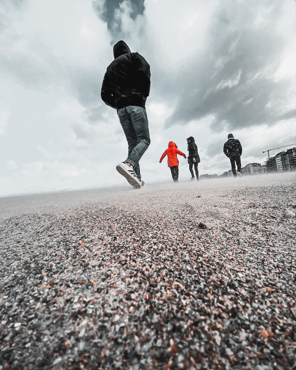 man in black jacket and blue denim jeans walking on gray sand during daytime
