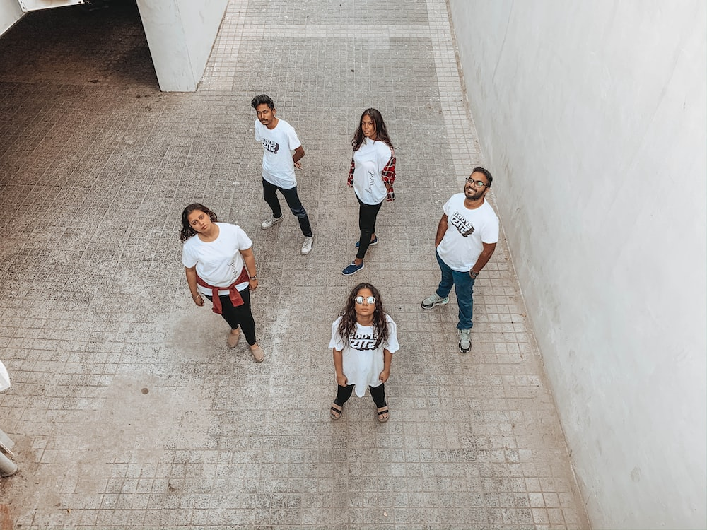 group of people in white shirt and black pants standing on gray concrete floor