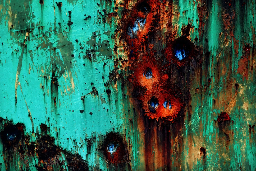 Brightly painted green-blue abstract wall texture with bullet dents surrounded by rust flow.