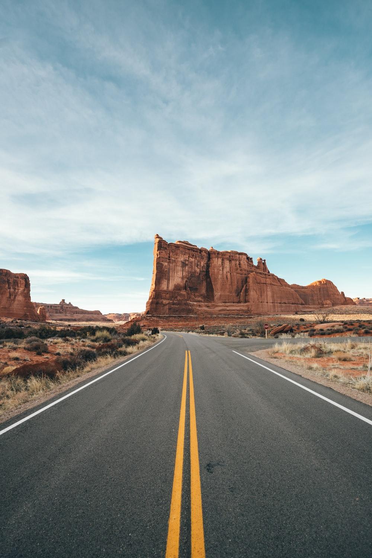 brown rock formation beside gray asphalt road during daytime