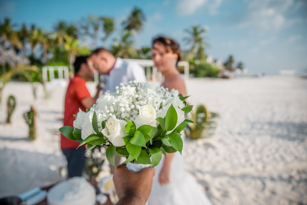 woman in white wedding dress holding bouquet of white flowers