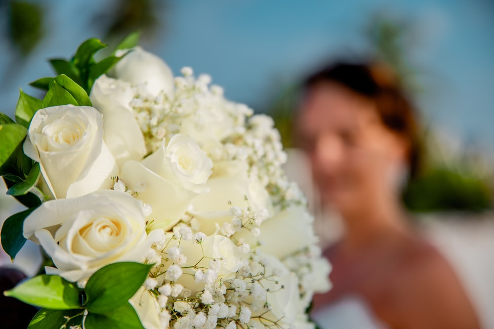 white rose bouquet in front of man