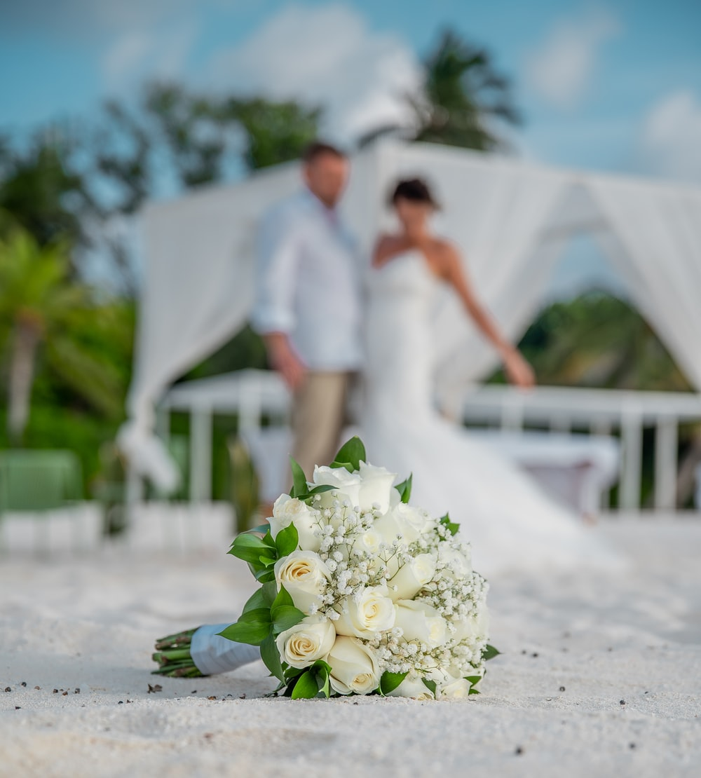 man in white dress shirt and woman in white dress holding bouquet of white roses