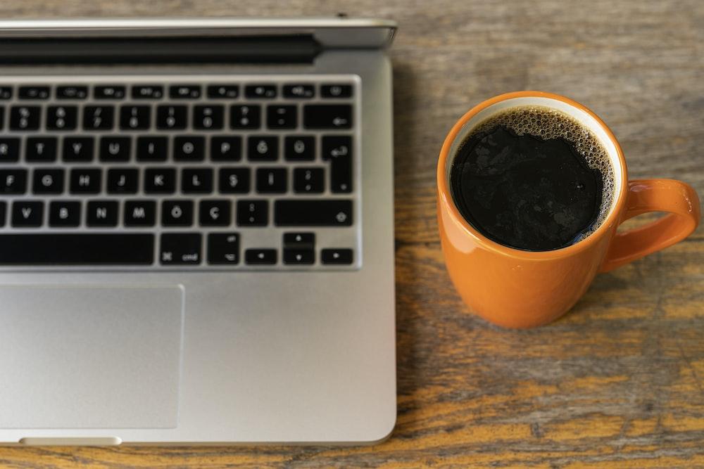 black coffee in orange ceramic mug beside macbook pro