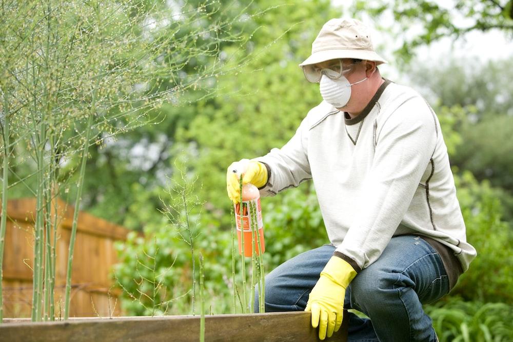 白い長袖シャツと中に茶色の木製のフェンスの上に座って青いデニムジーンズの男