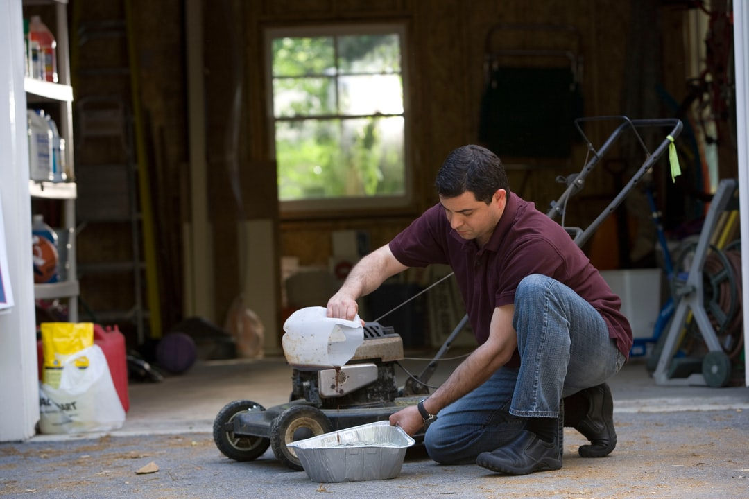 This man was in the process of changing his lawnmower's oil, using a disposable aluminum catch pan, which was filled with absorbent cat litter, both of which would be discarded in a safe, eco-friendly manner. Though the act of mowing one's lawn is rigorous, it is a great form of exercise, which exposes one to fresh, outdoor air, and sunshine. However, precautions need be taken against the inhalation of airborne irritants and pollutants, as well as against the suns powerful rays, by appropriately applying sunscreen to exposed skin.