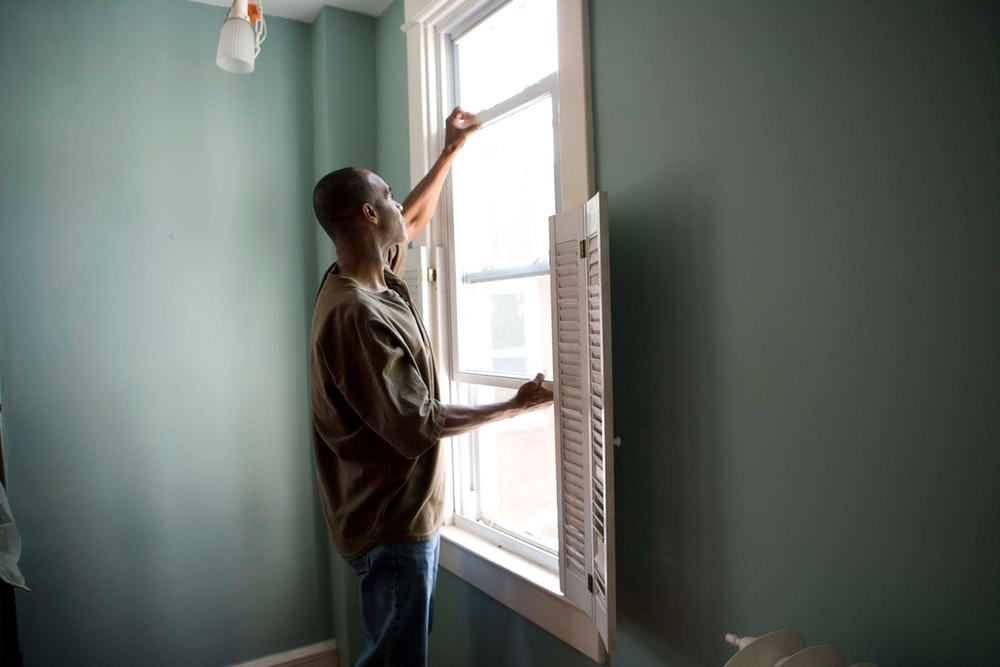 man in brown shirt and blue denim jeans standing near window