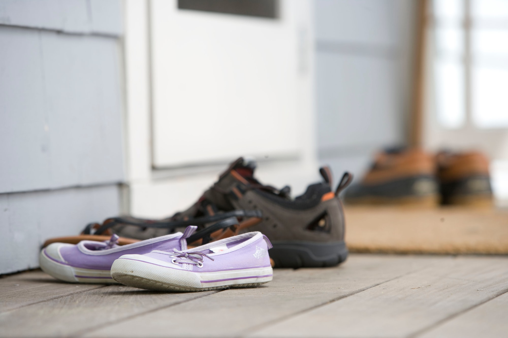 Outdoor contaminants such as pollutants and airborne particulates, always seem to find their way into even the cleanest homes. Keeping a home's interior free of such irritants, including allergens, dust, and pesticides, means leaving contaminated clothing at the door. In this particular photograph, four pairs of footwear had been left on the front porch so as to not track attached particulates into this house. Note that in this particular instance there is a door matt upon which one can wipe his, or her feet, prior to entering the home.