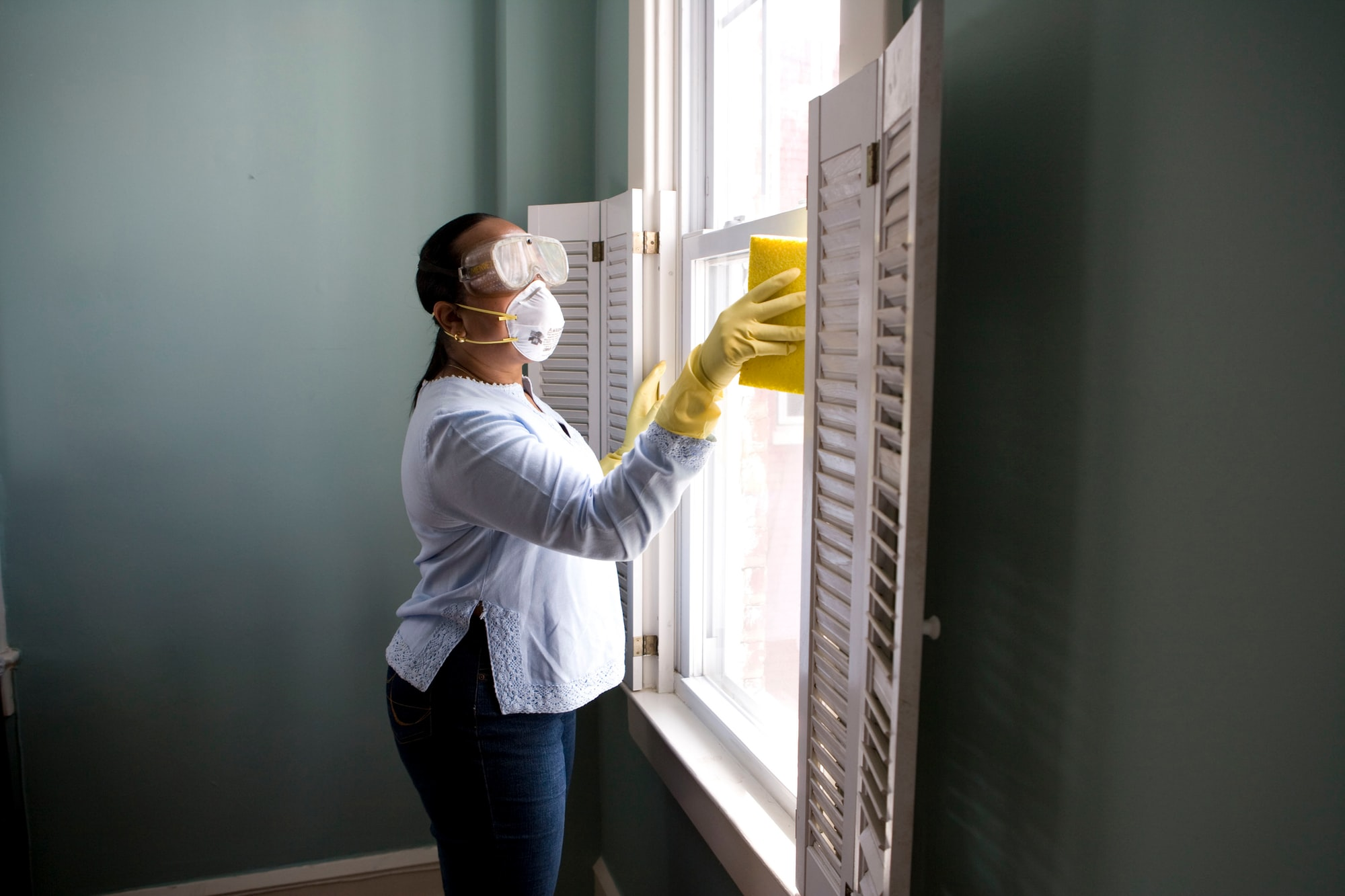 When renovating a home, you should use a damp sponge or cloth to clean dust collected on a window sill, as the dust may contain asbestos or lead-based paint. Home maintenance is an ongoing process for any homeowner, and here we see an African- American woman who'd taken a damp sponge to her window's frame, in order to remove accumulated dust particulates. Note how the homeowner had donned a pair of waterproof gloves, a facemask, and a pair of goggles, prior to beginning this task.