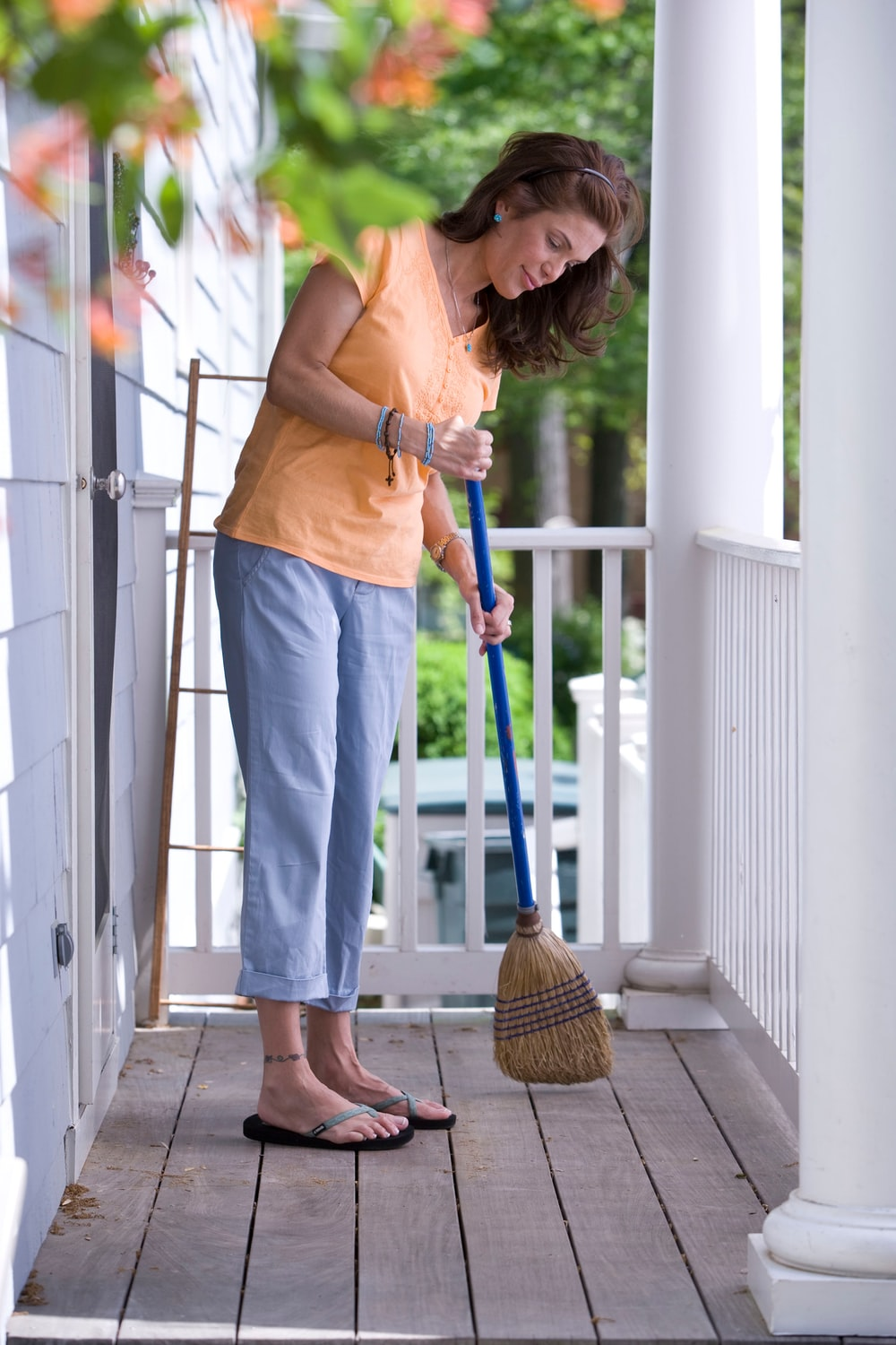 Woman in orange shirt and a broom sweeping a front porch