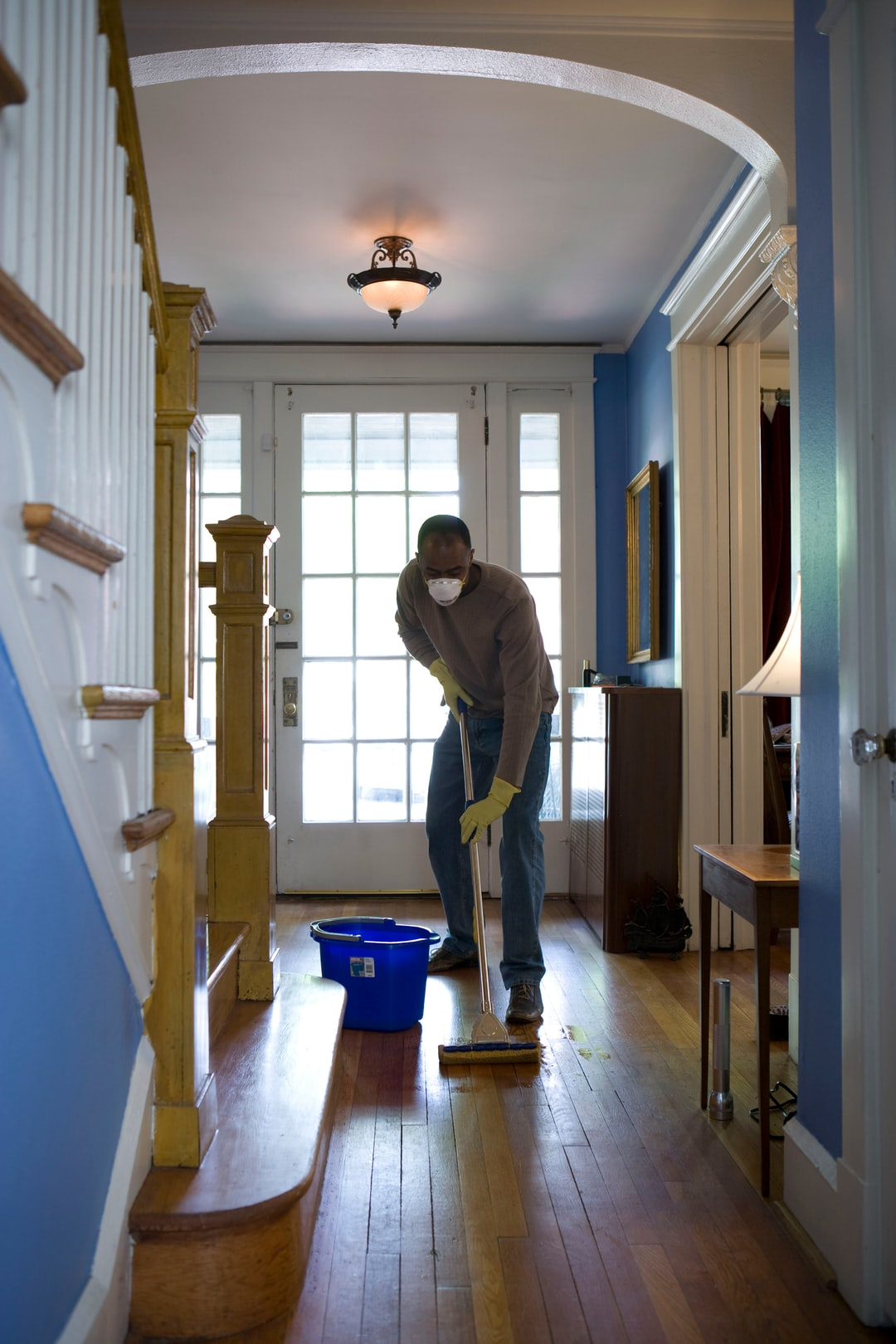 This African-American man was in the process of damp-mopping his home's entrance way. In this way airborne particulates including dust and pollen, could be removed from the inside of his home, thereby, reducing the detrimental effects these substances have upon the respiratory system of his family members. These irritants can sometimes result in sinus infections, and asthma.