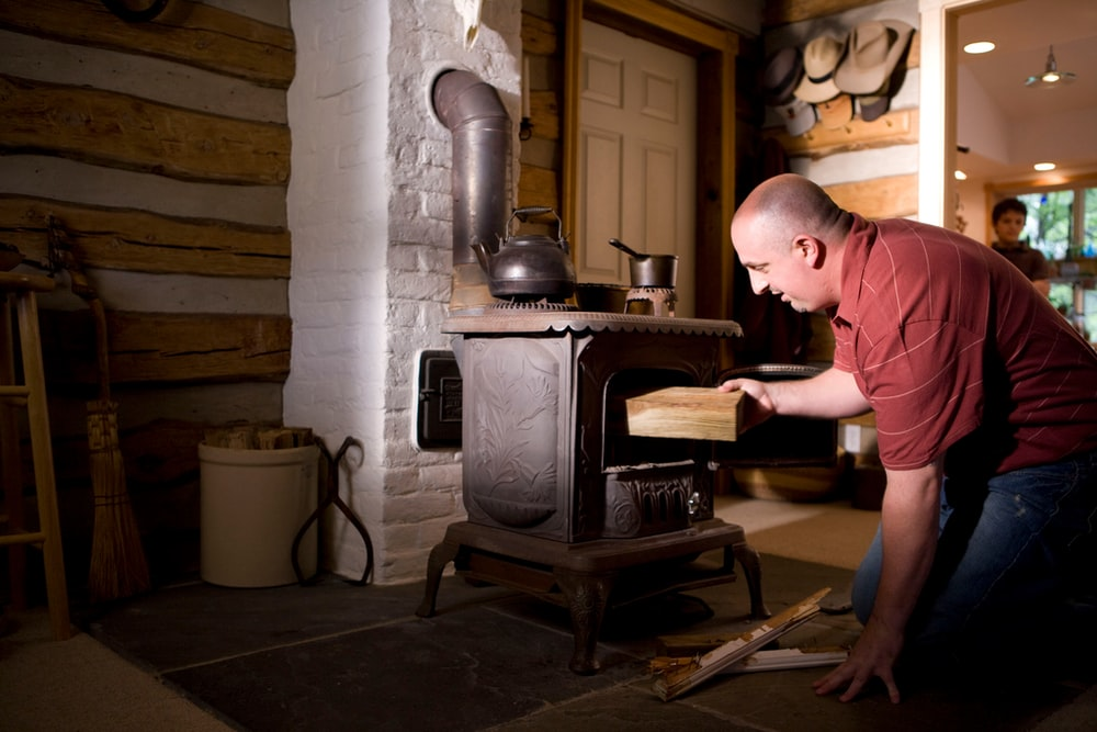 man in pink polo shirt and blue denim jeans standing in front of black wood burner
