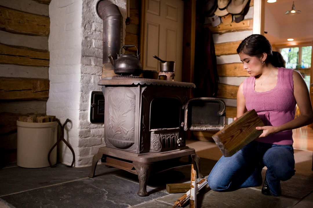 This home's interior, though beautiful, houses a potential hazard on many levels, therefore, special care need be taken in order to safely operate this wood-burning stove, for not only does it generate a terrific amount of heat, it does so using flame, rather than electricity, which is much more difficult to control. This woman was about to place what appears to be a piece or treated lumber into the stove as fuel.