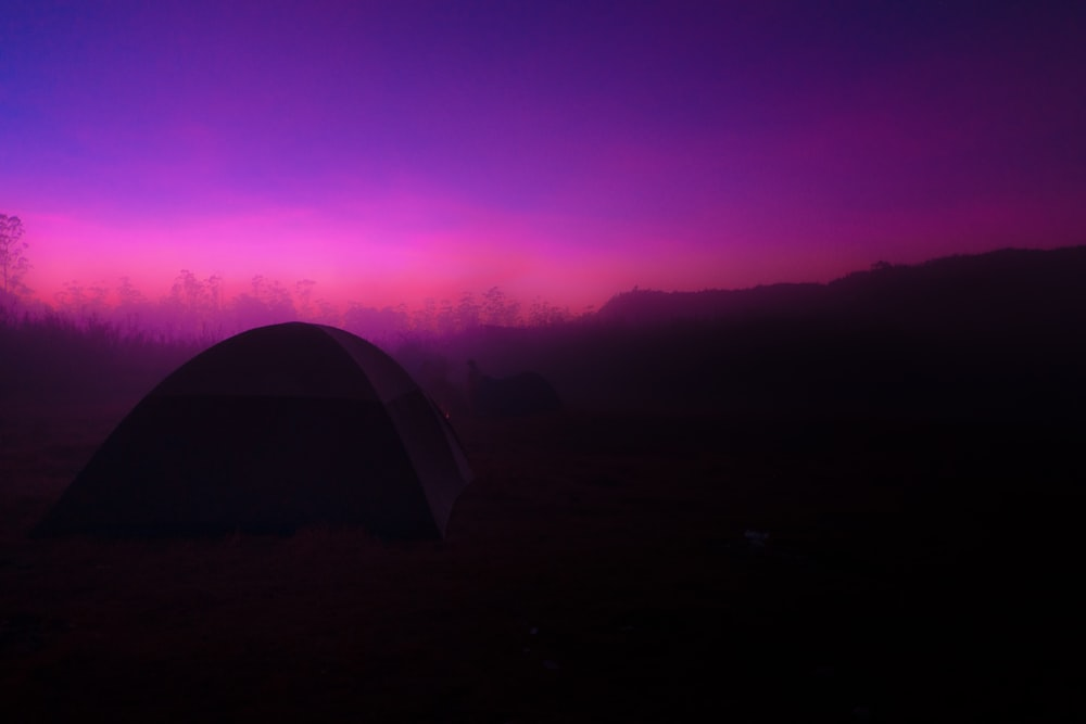 tent on green grass field during sunset