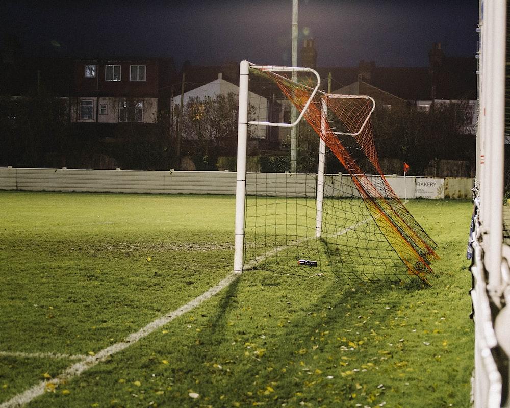 white metal soccer goal net on green grass field