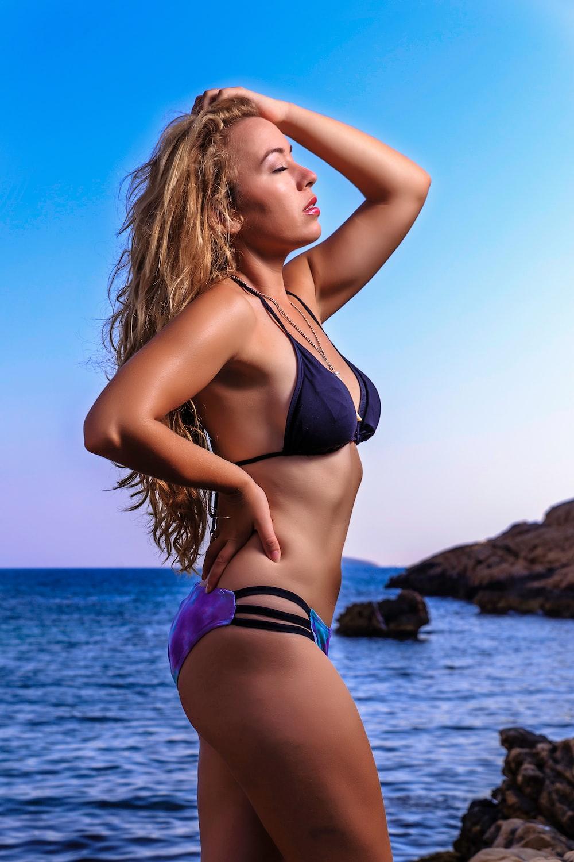 woman in black bikini bottom and black brassiere on beach during daytime