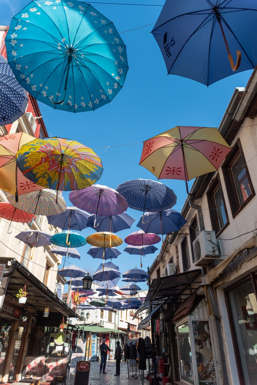 assorted umbrellas hanging on wire during daytime