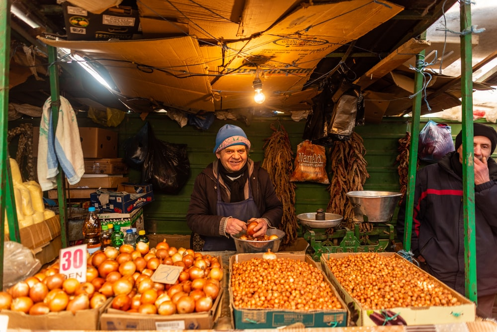 woman in brown jacket standing in front of fruit stand