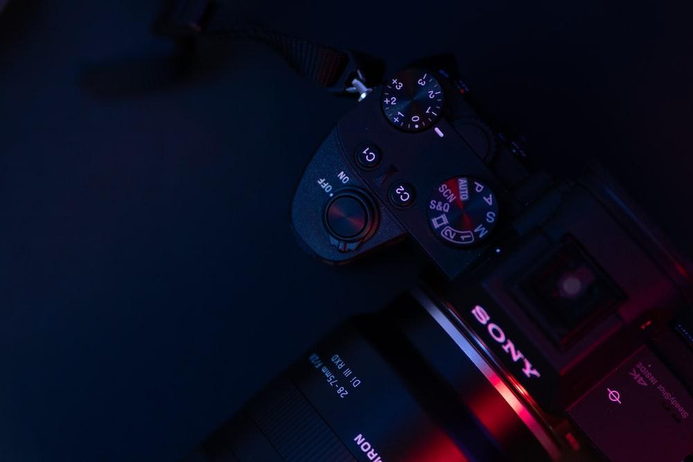 black sony dslr camera on black surface
