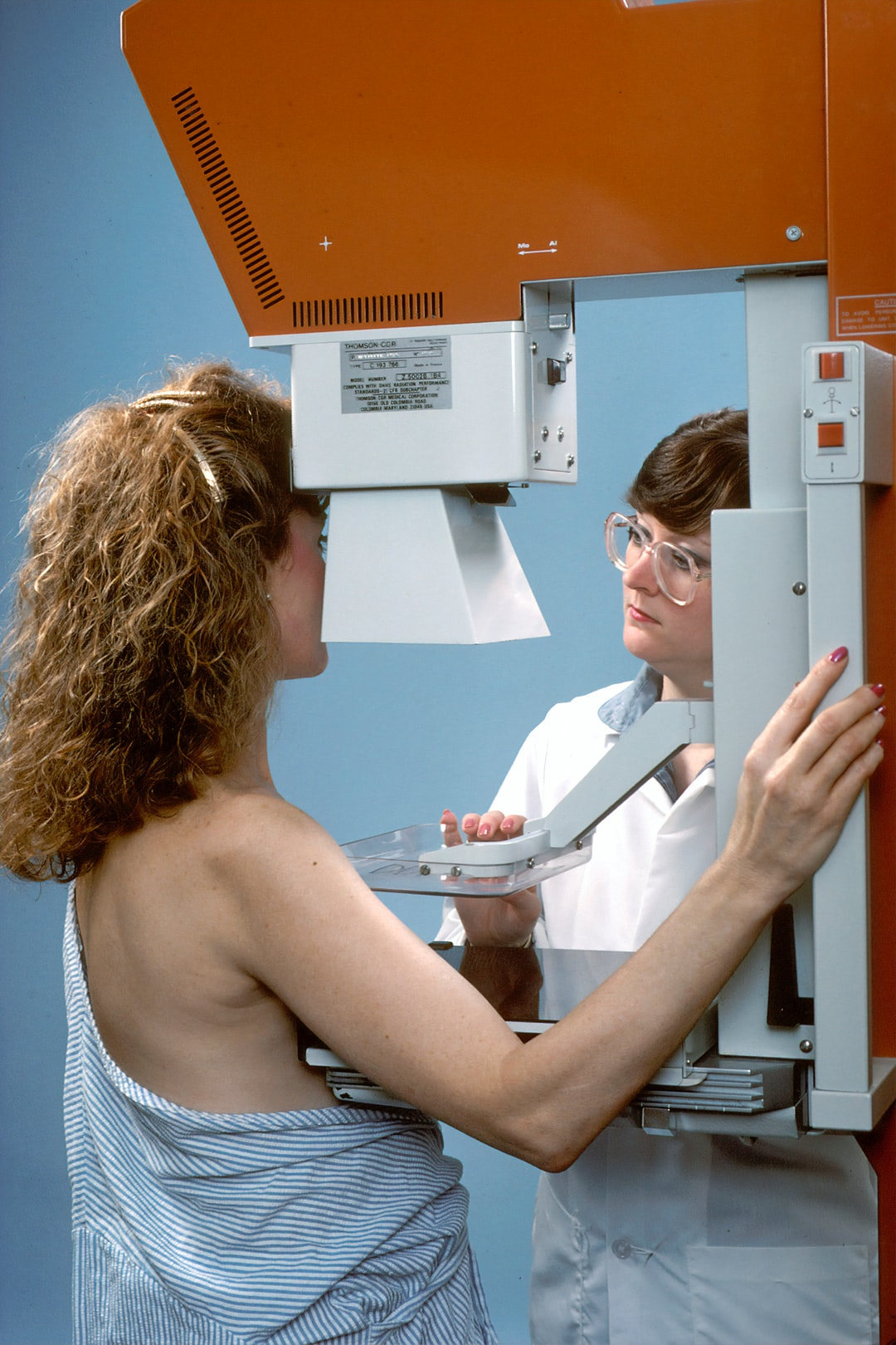 A female Caucasian radiology technician preparing a 42 year old Caucasian woman for a mammogram. The technician is positioning the paddle used to compress the breast. The patient's face is turned towards the technician, away from the camera. Her right shoulder is raised obscuring the breast.
